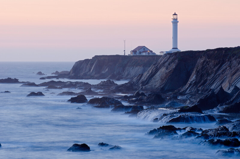Point Arena Light at dusk with waves in the foreground