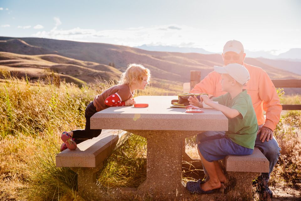 A man and two young children sit at a picnic table in Wenatchee, Washington.