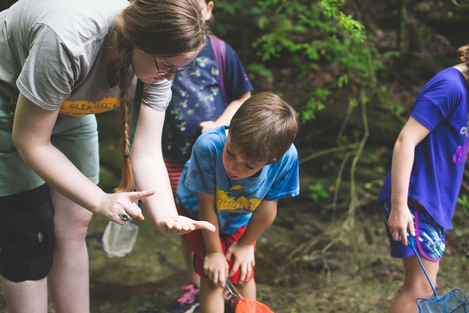 A camp counselor shows a boy a bug.