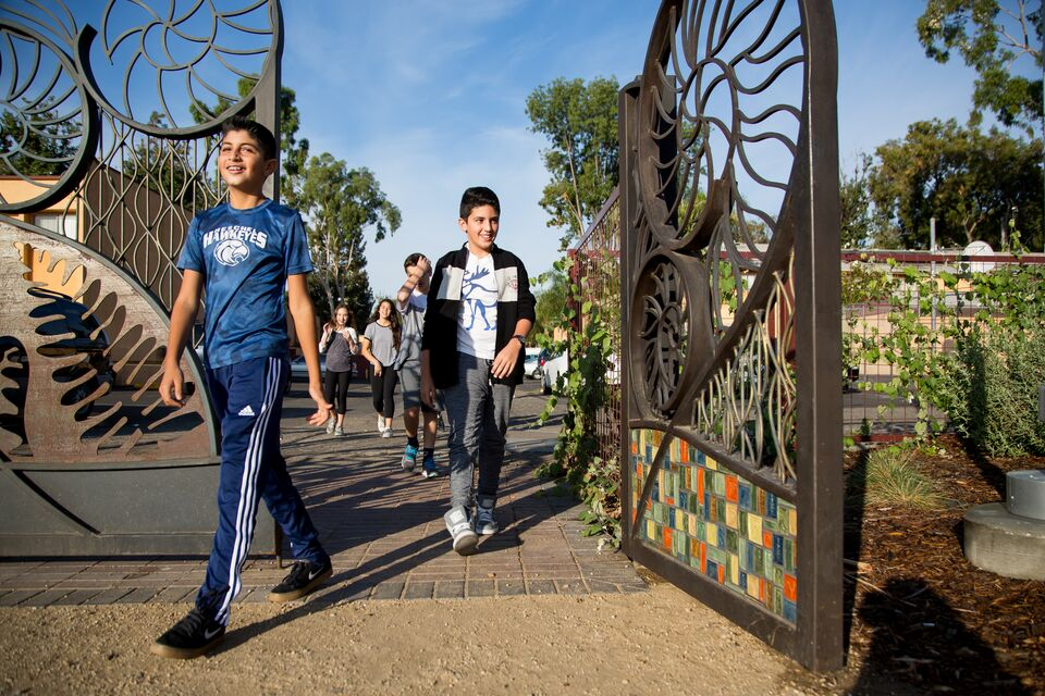 Two children walk through a decorative iron gateway to a city park