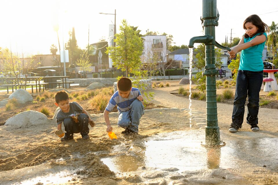 Three kids play at a water pump in a park