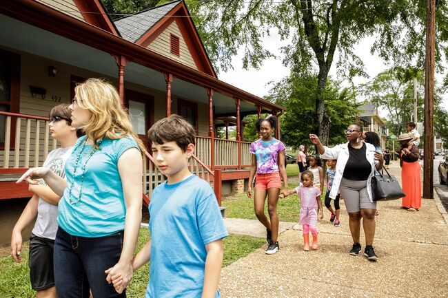 Families walk on a sidewalk in front of old houses