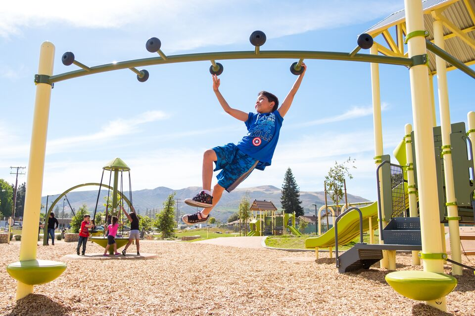 A boy swings on a playground in the sun